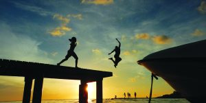 Local kids jumping from a pier at sunset. Photo was taken during snorkeling.